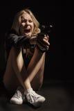 Girl with gun. Screaming girl with gun in dark stock photography