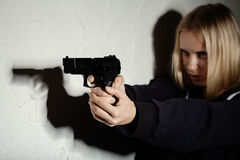 Girl with gun. Serious girl with gun aiming on wall background with copyspace stock photo