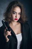 Girl with gun. Serious girl with gun on black background stock image