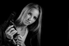 Girl with gun. Serious girl with gun on black background with copyspace, monochrome Stock Image