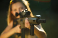 Girl with a gun for trap shooting aiming at a target Royalty Free Stock Images