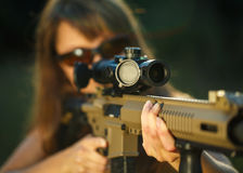 Girl with a gun for trap shooting and shooting glasses aiming at Royalty Free Stock Photos