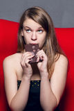 Girl with gusto eats a chocolate Royalty Free Stock Image