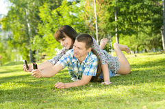 Girl and  guy. Young beautiful guy and the girl, lay on a lawn,  Photographed  each other, on cellular phones.   Adobe RGB (1998 Stock Image