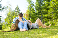 Girl and  guy. Young beautiful guy and the girl, sits on a lawn, kisses .  Adobe RGB (1998 Royalty Free Stock Image