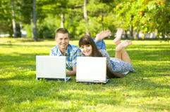 Girl and  guy. Young beautiful guy and the girl, lay on a lawn, have a good time about with laptop.  Adobe RGB (1998 Stock Images