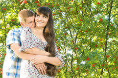 Girl and  guy. Young beautiful girl and the guy, embrace under a bush of a mountain ash, a happy smile.  Adobe RGB (1998 Stock Images