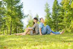 Girl and  guy. Young beautiful guy and the girl, sits on a lawn, Having leant to each other backs  Adobe RGB (1998 Royalty Free Stock Photography