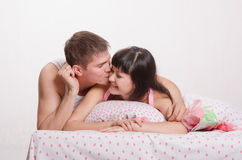 Girl with a guy in bed kissing Stock Photos