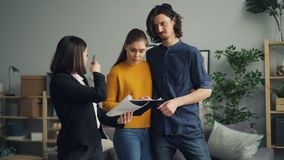Girl and guy buyers talking to housing agent reading contract in new apartment. Girl and guy buyers are talking to female housing agent reading contract in new stock footage