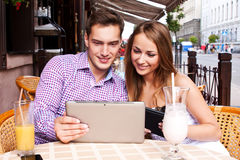 Girl with a guy in a cafe used  tablet computer Royalty Free Stock Photos