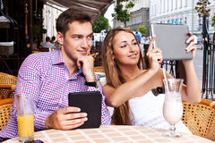 Girl with a guy in a cafe used  tablet computer Royalty Free Stock Photography