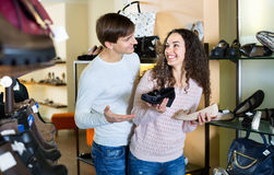 Girl with  guy choosing summer women shoes Stock Images