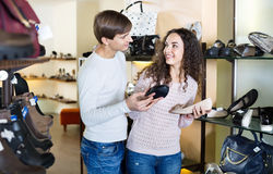 Girl with  guy choosing summer women shoes in a shoe store Royalty Free Stock Photos