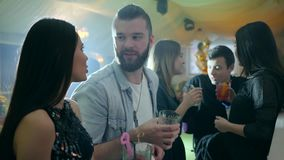 Girl and guy communicates with cocktails near bar counter against the background of a company of friends in a club stock footage