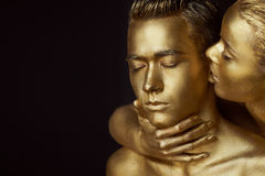 A girl and a guy covered in gold paint. With my eyes closed. The girl leaned in and kisses his ear Stock Image