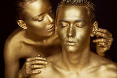 A girl and a guy covered in gold paint. With my eyes closed. The girl leaned in and kisses his ear Stock Photography
