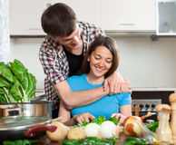 Girl and the guy cuts vegetables Royalty Free Stock Image