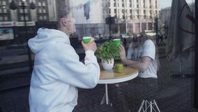 Couple on a date sit in a cozy cafe and drink coffee, and on their round table lies green apple and stands a flower stock footage