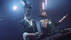 Girl and guy DJs in halloween costumes dance on scene playng music on turntable. Girl and guy DJs in halloween costumes dance on scene playing music on turntable stock footage