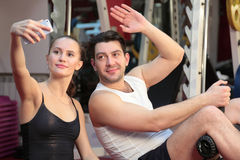 Girl with a guy doing selfie in the gym Stock Images