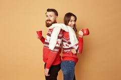 Girl and a guy dressed in red and white sweaters with deer and white knitted scarf stand back to back and hold red cups stock photo