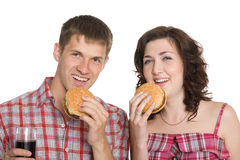 Girl and a guy eating cheeseburgers Royalty Free Stock Images