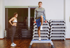 The girl and the guy are engaged in fitness step. A girl and a boy doing fitness step, the guy the coach shows the exercise. The concept of health Stock Images