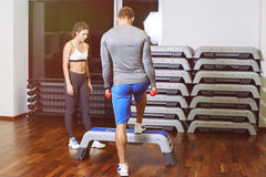 The girl and the guy are engaged in fitness step. A girl and a boy doing fitness step, the guy the coach shows the exercise. The concept of health Royalty Free Stock Photo