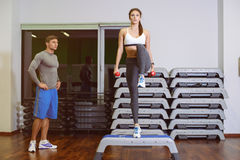 The girl and the guy are engaged in fitness step. Girl and a boy doing fitness step, men coach. The concept of health Stock Images