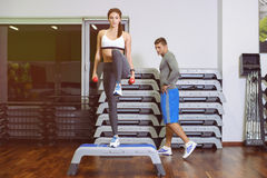 The girl and the guy are engaged in fitness step. Girl and a boy doing fitness step, men coach. The concept of health Royalty Free Stock Image
