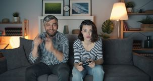Girl and guy enjoying video game at home late at night, woman winning. Girl and guy cute young couple are enjoying video game at home late at night using stock footage