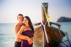 Girl and guy hug against longtail boat Royalty Free Stock Photography