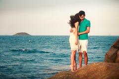 girl and guy hug on stone against azure sea Stock Photos