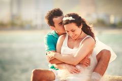 girl and guy hug on stone against sea Royalty Free Stock Photo