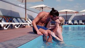 Girl and guy kissing, couple in love kiss, swimming in the pool, female emerges from the water, relax in the hot spa stock footage