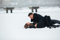 Girl and guy lie on snow Stock Image
