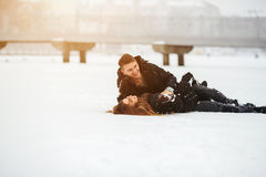 Girl and guy lie on snow. In the park, in winter holidays Stock Image