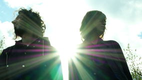 Girl and guy look at each other. With sun flare behind them stock footage