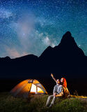 Girl and guy looking at the shines starry sky at night. Couple sitting near camping Royalty Free Stock Image