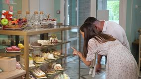 Girl and guy looks at tasty cakes in shop glass show case. Lovely girl and guy looks at different tasty cakes choosing dessert on show case shelves in modern stock video footage
