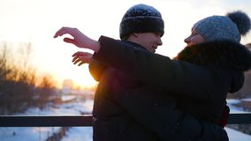 Girl and guy meet on the bridge and hugging at sunset stock video
