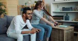 Girl and guy mixed race couple are enjoying video game at home using joysticks. Girl and guy cute mixed race couple are enjoying video game at home using stock footage