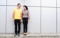 Girl and guy near the wall of the office building. Love Story happy girl and guy in office Royalty Free Stock Photo