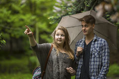 Girl with the guy in the Park talking under an umbrella. Love. Stock Photo