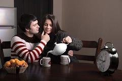 Girl guy pours tea. Girl pours tea guy, while the guy stroking her face Stock Photos