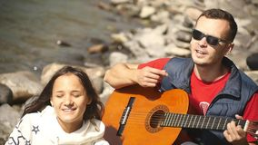 A girl and a guy rest on the river bank, sing songs to the guitar stock video footage