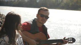 A girl and a guy rest on the river bank, sing songs to the guitar stock video