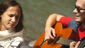 A girl and a guy rest on the river bank, sing songs to the guitar stock footage