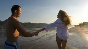 A girl and a guy running around on the beach stock video footage